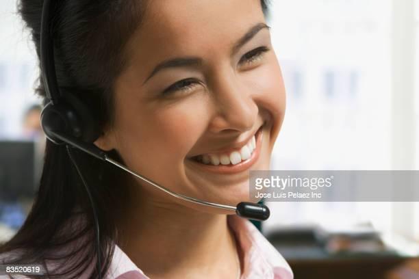 Asian businesswoman talking on telephone headset