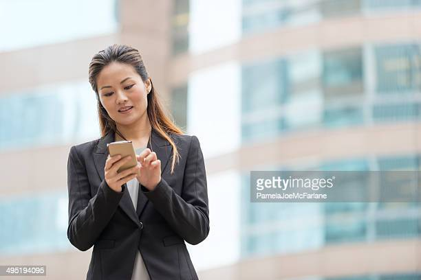 Asian Businesswoman Texting in Front of an Office Building
