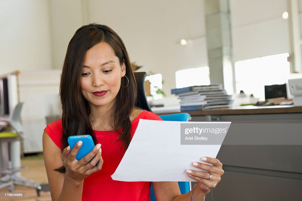 Asian businesswoman using cell phone at desk : Stock Photo