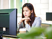 young asian female corporate executive working in office using computer.
