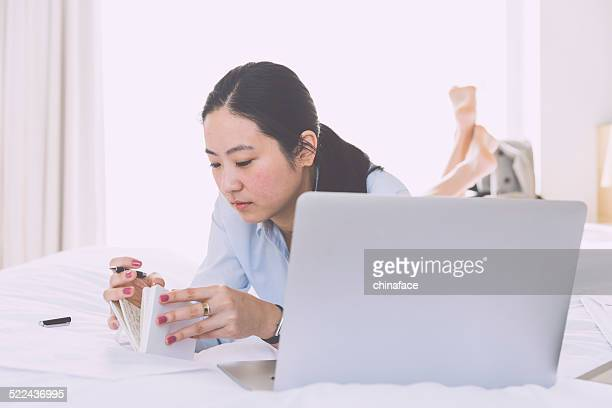 asian businesswoman working on bed in hotel