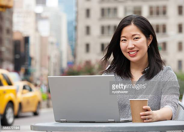 Asian Businesswoman working on computer in City outdoors