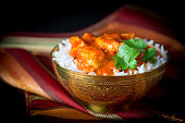 Bowl of butter chicken on a bed of basmati rice.