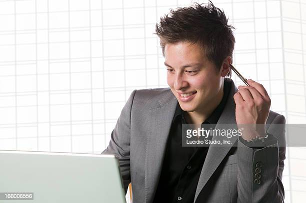 Asian Caucasian mixed race businessman with a lapt