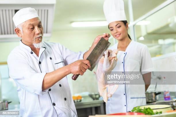 Asian chef preparing chicken meat
