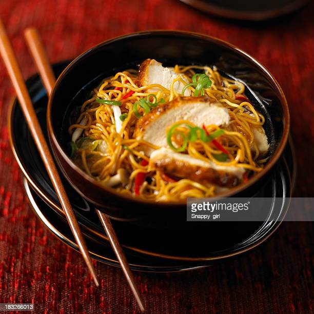 Asian chicken soup with udon noodles eaten with chopsticks
