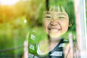 Asian child girl standing on glass mirror reflecting green forest. She was smiling in a good mood.