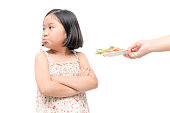 asian child girl with expression of disgust against vegetables isolated on white background, Refusing food concept