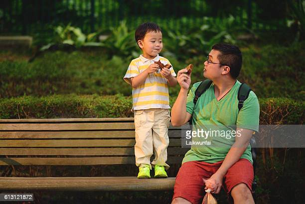 Asian child share food with father