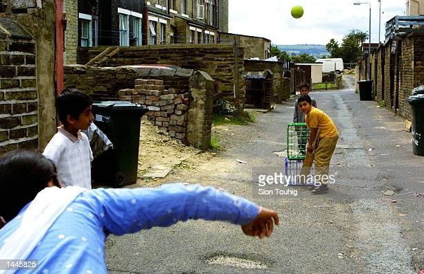 Asian children play cricket in an alley in the Manningham district of Bradford July 14 2001 in England The neighborhood has been the site of recent...