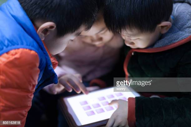 Asian children playing with digital tablet