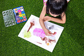 Asian Chinese little girl lying on the grass drawing and painting