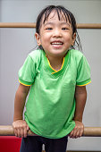 Asian Chinese little girl hanging on uneven bars in gym class