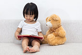 Asian Chinese little girl reading book with teddy bear on the sofa in the living room.