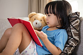 Asian Chinese little girl reading book with teddy bear on the couch in the living room at home.