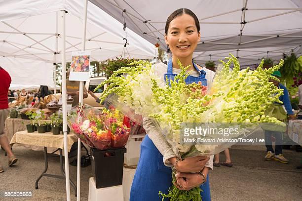 Asian clerk holding fresh flowers at farmers market