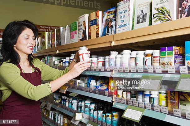 Asian clerk shelving in natural medicine store