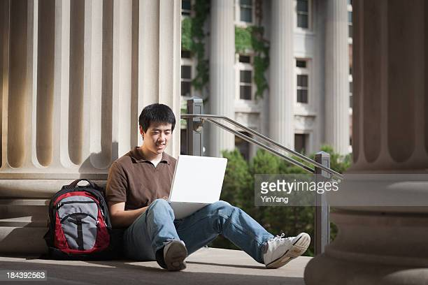 Asian College Student Studying Computer Laptop by University Campus Building