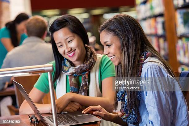 Asian college student tutors high school student in library