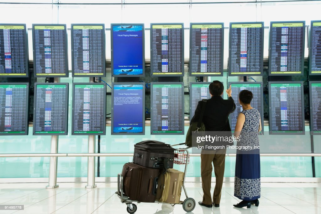 Asian couple checking flight schedules in airport