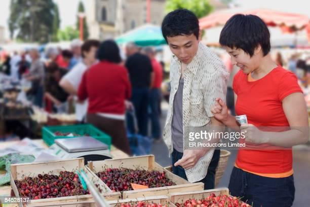 Asian couple choosing cherries at outdoor market
