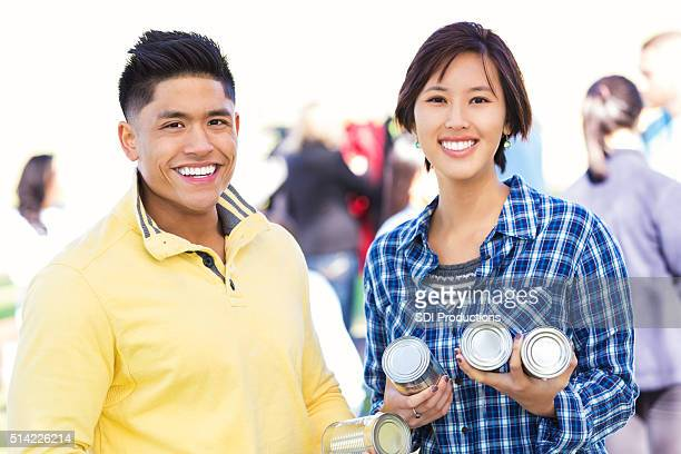 Asian couple donating items at food drive