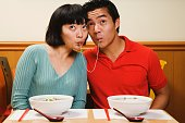 Asian couple eating same noodle