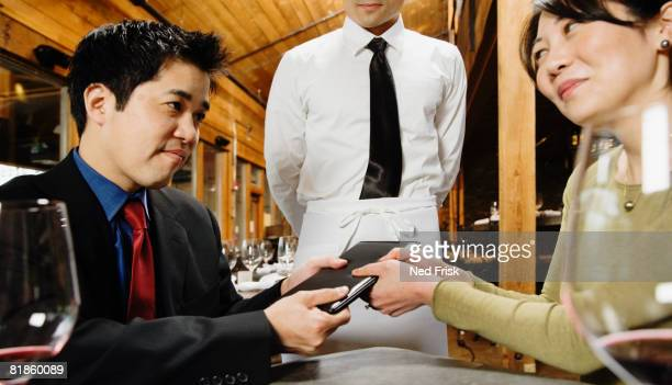Asian couple fighting over restaurant bill