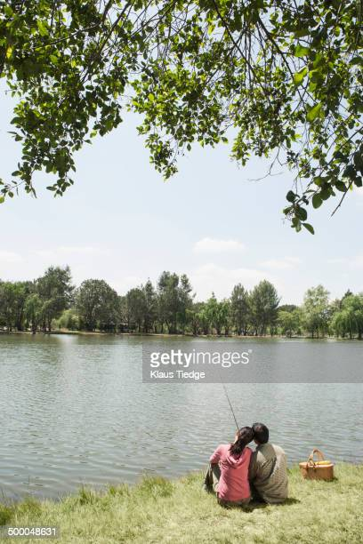 Asian couple fishing in rural lake