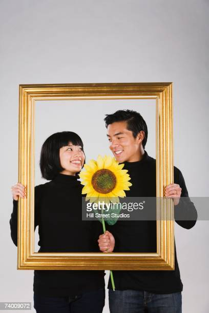 Asian couple holding flower inside picture frame