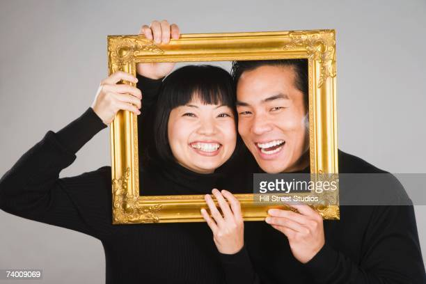 Asian couple holding picture frame around faces
