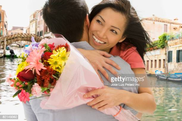 Asian couple hugging with flowers