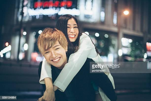 Asiatische Paar im Huckepack nehmen Sie auf der Straße bei Nacht