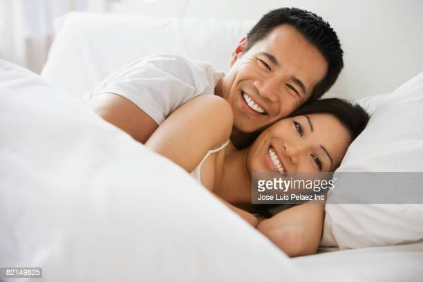 Asian couple laying in bed