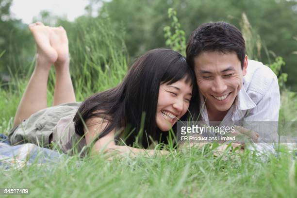 Asian couple laying in grass