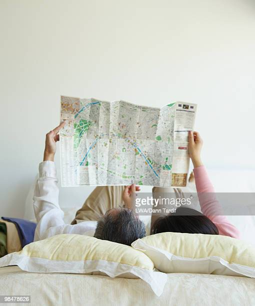 Asian couple looking at map in bedroom