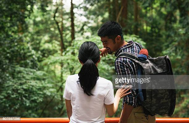 Asian Couple Looking into Distance in Woods