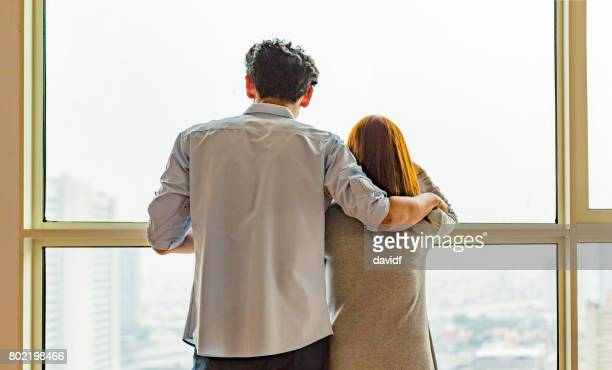 Asian Couple Looking Out a Window