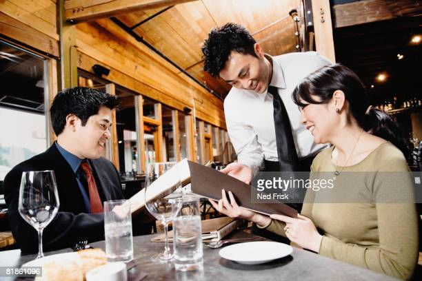 Asian couple reading menu at restaurant