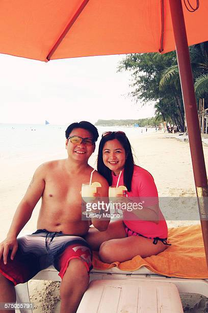 Asian couple relaxing at beach sipping pina colada
