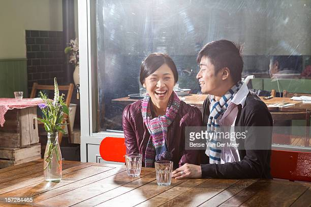 Asian couple sitting at table outside cafe