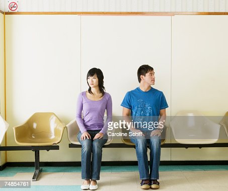 Asian couple sitting in waiting area