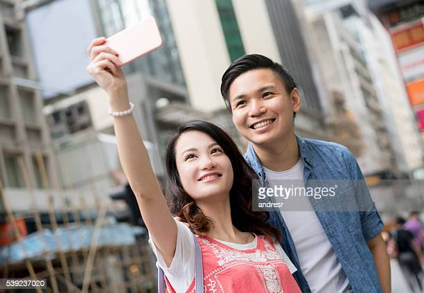 Asian couple taking a selfie on the street