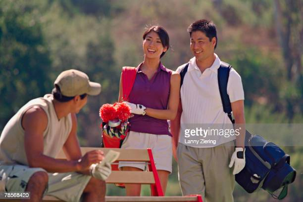 Asian couple talking to man on golf course