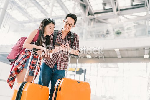 Asian couple travelers using smartphone checking flight or online check-in at airport, with passport and luggage. Air travel or mobile phone technology concept : ストックフォト