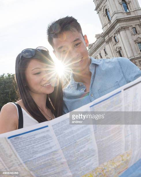 Asian couple traveling and looking at a map