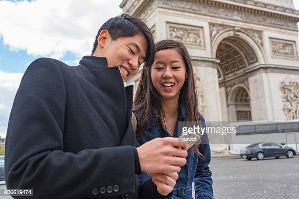 Asian Couple Using Phone For Ride Sharing Taxi in Paris