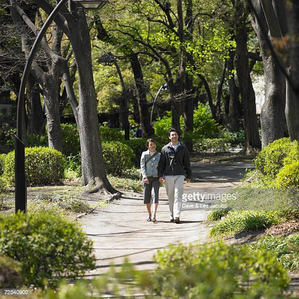 Asian couple walking and holding hands in park
