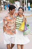 Asian couple walking on sidewalk