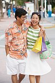 Asian couple walking on sidewalk